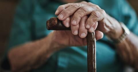 senior leunend met handen op wandelstok