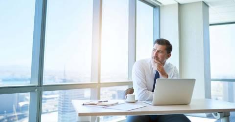 Zakenman op kantoor die optimistisch wegkijkt